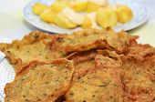 stock photo of torta  - closeup of a plate of spanish shrimp cakes and patatas bravas in the background - JPG