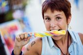 Young brunette enjoying her ice lolly.