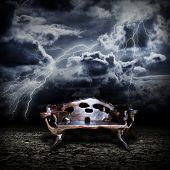 stock photo of throne  - Majestic wooden throne standing on the abandoned land during a storm - JPG