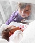 Newborn baby girl in a incubator. Her sister looking at.