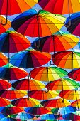 Street Art Of Many Multicolored Decorative Umbrellas Along Street Passage Covering The Sky. poster