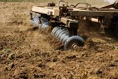 stock photo of cultivator-harrow  - part ot agricultural tractor cultivating land - JPG