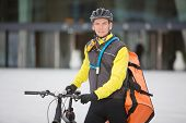 Portrait of young male cyclist in protective gear carrying courier delivery bag