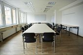 Empty clean conference room with whiteboard and tables and chairs
