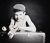 vintage art portrait of little boy looking at camera holding catapult and  leaning on old suitcase,