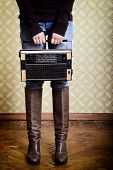 young woman holding radio player in room with vintage wallpaper, legs detail, retro stylization 60-70s, toned