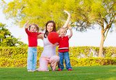 stock photo of waving hands  - Mother with two cute kids raising hands up and enjoying sunny day - JPG