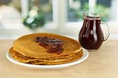 Sweet pancakes on plate with jam on table in kitchen