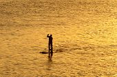 silhouette of man paddleboarding in open water