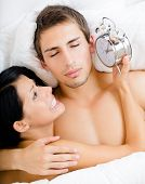 Close up of couple lying in bed. Woman holds alarm clock near the ear of man, top view