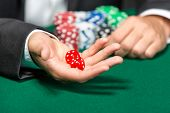 pic of gambler  - Player throws dices on the poker table - JPG