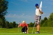 Junge weibliche Golfspieler auf dem Platz setzen, sie mit dem Ziel, für ihr Put erschossen