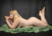 Naked blonde woman eating fresh ripe banana on black background. Funny image - Fine Art style. Great for calendar.