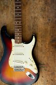 pic of fret  - Sunburst color guitar with very old wood surface in background - JPG