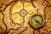 Vintage compass lies on an ancient map of the North Pole (also Hyperborea). Arctic continent on the