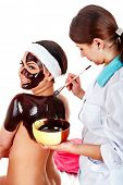 Girl having chocolate body mask apply by beautician. Isolated.