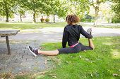 Rear view of a flexible young woman doing the splits exercise in the park