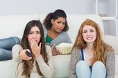 Portrait of scared young female friends with remote control and popcorn bowl on sofa at home
