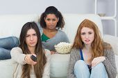 stock photo of slumber party  - Portrait of serious young female friends with remote control and popcorn bowl on sofa at home - JPG