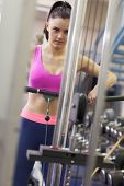 stock photo of lats  - Determined sporty young woman doing exercises in the gym on lat machine - JPG
