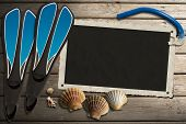 image of flipper  - Aged photo frame with seashells on beach blue flippers and blue snorkel diving on wooden floor with sand - JPG