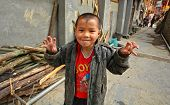 Asian Boy 8 Years Old, Playing In Street In Chinese Countryside.