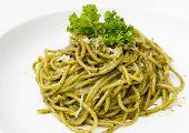 Italian pasta spaghetti with pesto sauce and basil leaf