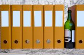 stock photo of debauchery  - Green bottle of wine between yellow data folders - JPG