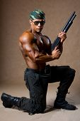 A Muscular Man With A Gun.