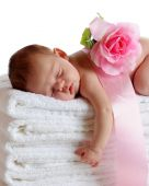 picture of newborn baby girl  - A beautiful newborn sleeping soundly on a stack of white towels a ribbon and pink rose on her back - JPG