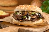 stock photo of cheese-steak  - A classic steak melt sandwich with green pepper and onions - JPG