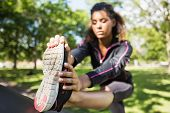 stock photo of slender legs  - Pretty sporty woman stretching her leg while standing in the park - JPG