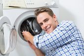 Portrait of a smiling technician repairing a washing machine
