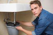 Portrait of handsome plumber repairing the drain of sink in bathroom