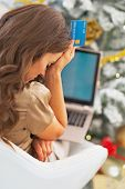 Stressed Young Woman With Credit Card And Laptop In Front Of Christmas Tree