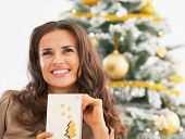 Portrait Of Happy Young Woman And Christmas Postcard Near Christ