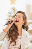 stock photo of christmas song  - Happy young woman singing in front of christmas tree - JPG