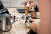 Cropped image of barista with portafilter and tamper in coffee shop