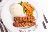 Adana Kebabs Served On A Lavash Bread Garnished With Vegetables And Rice Pilaf