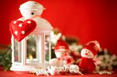 image of home is where your heart is  - Cute couple of little adorable snowmen is standing near the white fairy lantern with a toy heart on it and decorated fir tree branch behind it - JPG