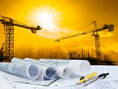 pic of construction crane  - architect plan on working table with crane and building construction background - JPG