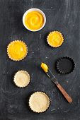 picture of curd  - Two delicious homemade lemon curd tartlets and two cooked shortcrust pastry served with dish of lemon curd cream taken from above on black chalky background with spatula - JPG