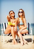 summer holidays and vacation - girls in bikinis with drinks on the beach chairs