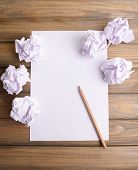 foto of stress-ball  - Sheet of white paper with crumpled  paper  and pencil on table close - JPG