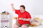Lazy overweight male sitting with fast food on couch and watching television