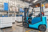 picture of heavy equipment operator  - forklift in the large modern warehouse - JPG