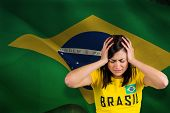 Upset football fan in brasil tshirt against digitally generated brazil national flag