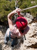 picture of hang-gliding  - Young girl over rocks going across tyrolean traverse