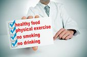 stock photo of physical exercise  - a man wearing a white coat sitting in a desk showing a signboard with some healthy habits - JPG