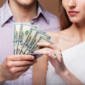 Loving Couple Are Holding A Large Sum Of Money. Business Kontseptsiya.semeyny Budget.